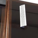 Maniglia adesiva applicata sull'anta di una vetrina di vetro